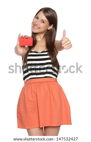 Smiling young woman showing blank credit card and gesturing thumb up, isolated on white background - stock photo