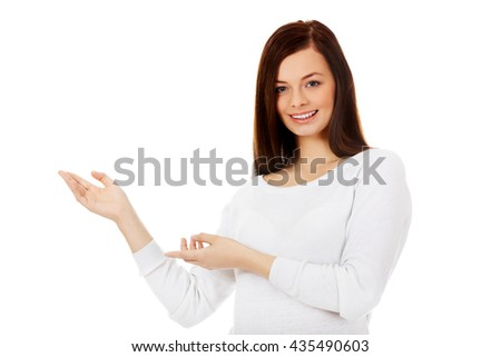 Smiling young woman shows something - stock photo