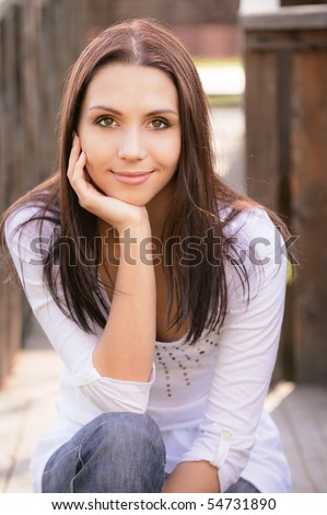 Smiling young woman sits on wooden porch. - stock photo