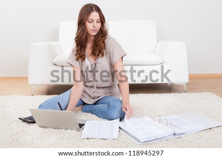 Smiling young woman sitting on the carpet with her papers and a laptop working in the living room - stock photo