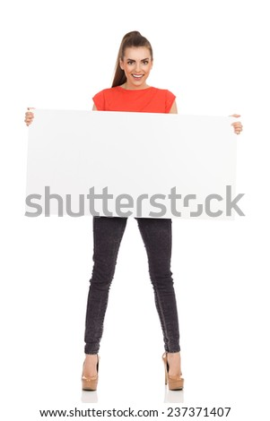 Smiling young woman standing and holding blank placard. Full length studio shot isolated on white. - stock photo