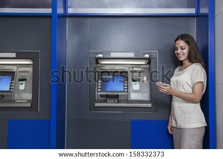 Smiling young woman standing in front of ATM and looking at her phone - stock photo