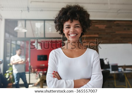 Smiling young woman standing with her arms crossed and looking at camera. She is standing in a modern office with her colleagues in the background. - stock photo