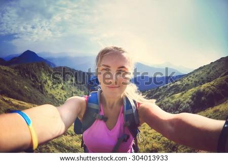 Smiling young woman takes a selfie  on mountain peak in Carpathian Mountains  - stock photo