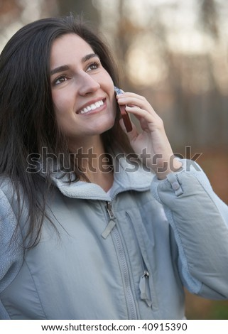 Smiling young woman talking on mobile phone outdoors - stock photo