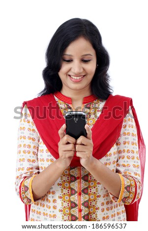 Smiling young woman texting on her mobilegainst white background - stock photo
