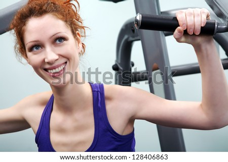 Smiling young woman training on sport machine in gym - stock photo