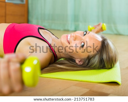 Smiling young woman training with dumbbells at home  - stock photo