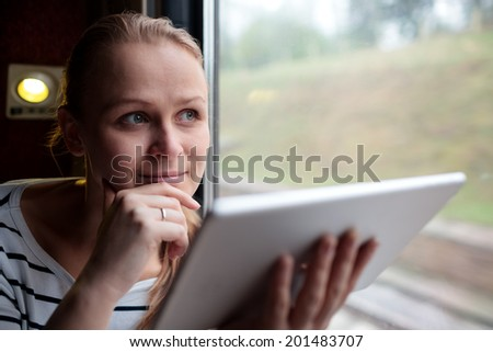 Smiling young woman traveling by train holding a tablet in her hands as she stares thoughtfully into the air through the window with her hand to her chin - stock photo