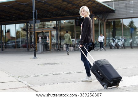 Smiling young woman traveling with a wheeled suitcase - stock photo