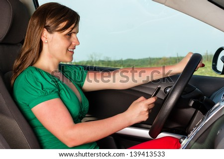Smiling young woman using her mobil phone while driving - stock photo