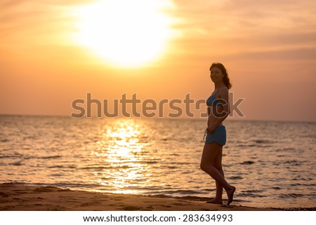 Smiling young woman walking on the sand beach at picturesque colorful sunrise or sunset, lit by warm sunlight, copy space - stock photo