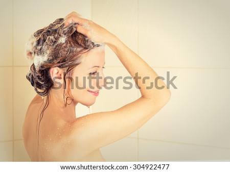 Smiling young woman washing head with shampoo in a shower    - stock photo