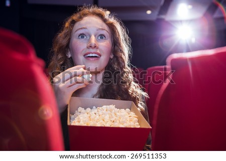 Smiling young woman watching a film at the cinema - stock photo