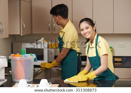 Smiling young woman wiping tabletop when man cleaning microwave - stock photo