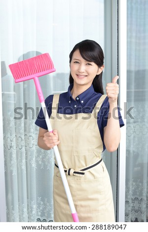 Smiling young woman with a broom sweeping the balcony  - stock photo