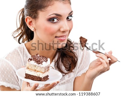 Smiling young woman with a cake slice on a plate - stock photo