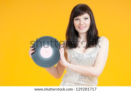 Smiling young woman with a vinyl disc over yellow background - stock photo