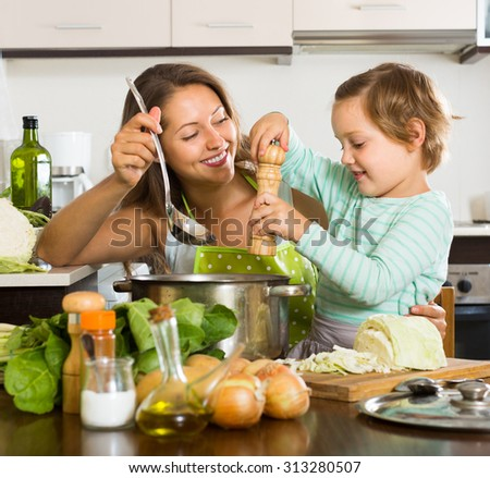 Smiling young woman with baby cooking soup at home kitchen. Focus on woman  - stock photo