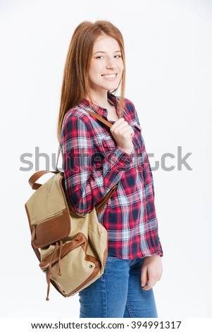 Smiling young woman with backpack standing isolated on a white background - stock photo