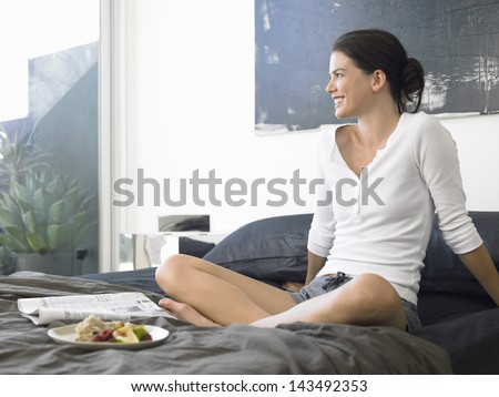 Smiling young woman with breakfast and newspaper on bed - stock photo