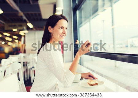 smiling young woman with cake and coffee at cafe - stock photo