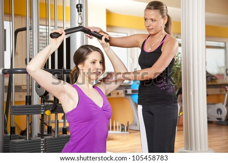 smiling young woman with her female coach training latissimus - stock photo