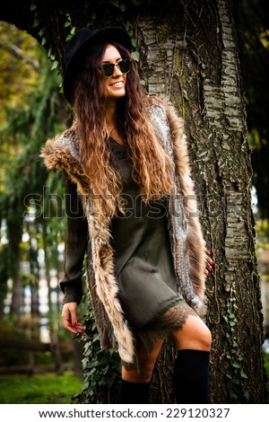 smiling young woman with long curly hair in park  wearing sunglasses, hat, fur vest and  green dress lean on tree - stock photo