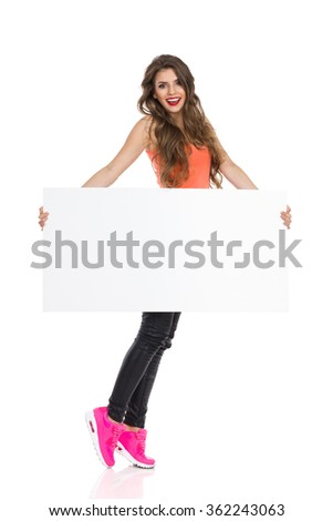 Smiling young woman with long hair orange shirt and pink sneakers standing tiptoe, holding blank placard and looking at camera. Full length studio shot isolated on white. - stock photo