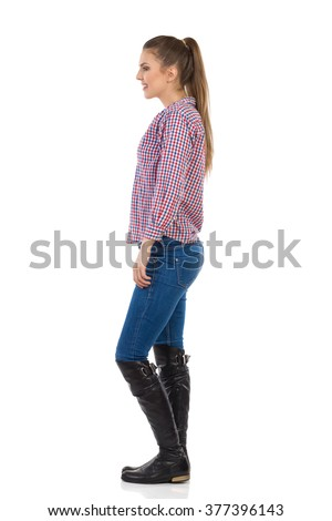 Smiling young woman with ponytail standing in jeans, black boots and lumberjack shirt. Side view. Full length studio shot isolated on white. - stock photo