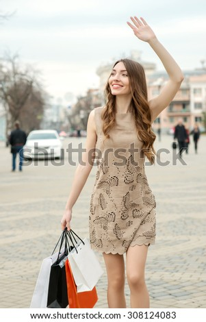 Smiling  young woman with shopping bags at the street in the city - stock photo
