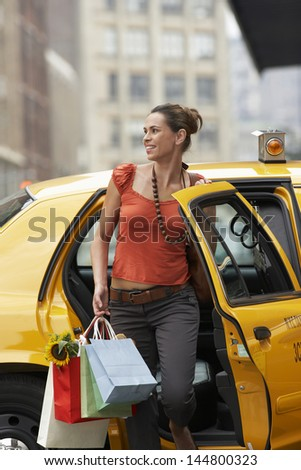 Smiling young woman with shopping bags exiting yellow taxi - stock photo