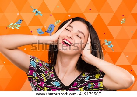 Smiling young woman, with straight dark hair, wearing on colorful shirt, posing on the orange geometric background with blue birds, in studio, waist up - stock photo