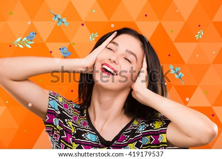 Smiling young woman, with straight dark hair, wearing on colorful shirt, posing on the orange geometric background with blue birds and colorful spots, in studio, waist up - stock photo