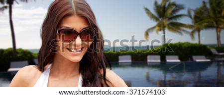 smiling young woman with sunglasses on beach - stock photo