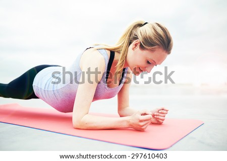 Smiling young woman working out during her pregnancy balancing on her elbows and toes in a pilates exercise to strengthen and control her muscles, close up view - stock photo