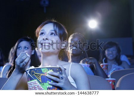 Smiling young women sitting and watching movie in the theatre - stock photo