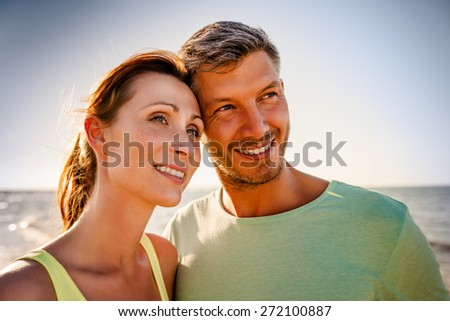 smiling younger couple after workout on the sea - stock photo
