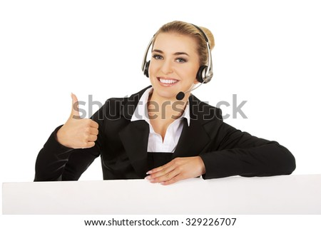 Smille call center woman holding empty banner and showing OK. - stock photo