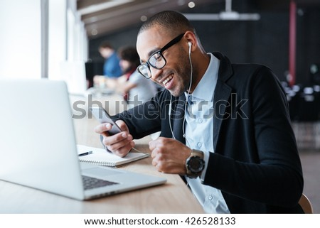 Smilling cheerful businessman texting message on the smartphone in front of the laptop in the office - stock photo