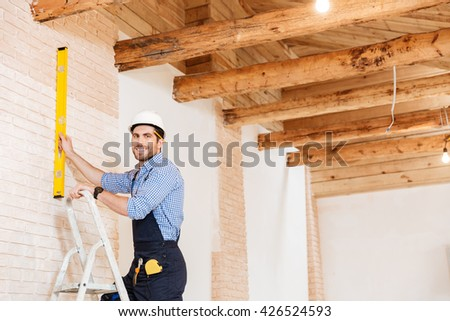 Smilling handsome builder using level and standing in the ladder at the working area indoors - stock photo