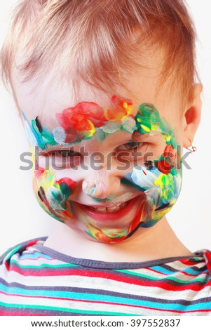 smilling happy cute little girl with colorful painted face - stock photo