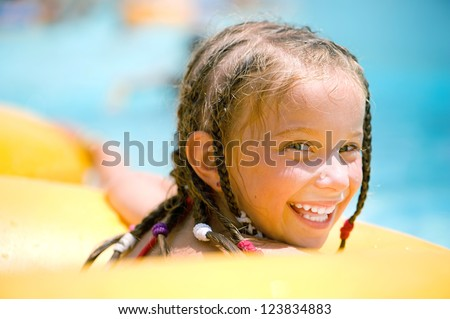 Smilyng little girl  sitting on inflatable ring in swimming pool. - stock photo