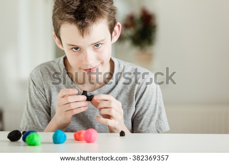 Smirking caucasian boy forming various sized balls from colorful clay on desk while looking at camera - stock photo
