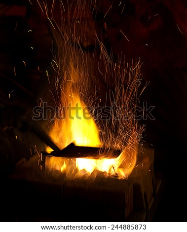 smithy fire flame tips with sparks closeup on dark background - stock photo