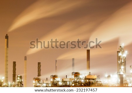 Smoke and chimneys of a large oil-refinery plant at night - stock photo