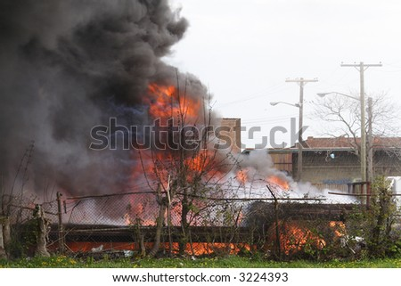 smoke and flames from a truck on fire in a shipping yard - stock photo