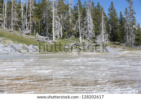 Smoke and steaming water coming out of  hot springs and geysers  in Yellowstone National Park, Montana, Wyoming, USA - stock photo