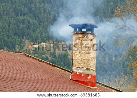 Smoke coming out of a chimney of a mountain house - stock photo