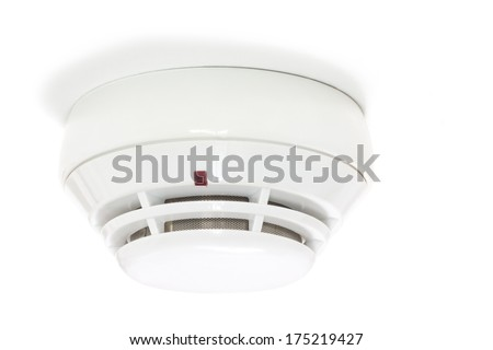 Smoke detector attached to the white ceiling - stock photo